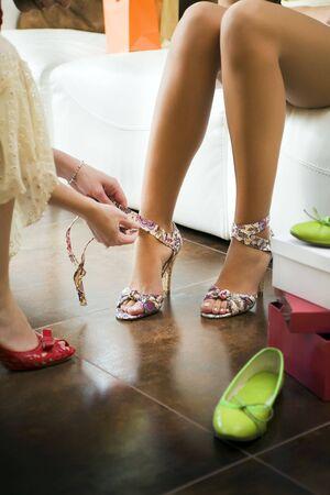 comprando zapatos: Mujer joven tratando de zapatos de tac�n alto, mujer atar las correas de los zapatos