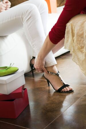sales clerk: Young woman trying on high heel shoes, woman tying straps of shoes