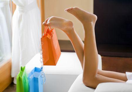 Young woman's legs dangling shopping bag Stock Photo - 3837476