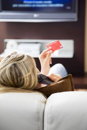 Young woman watching tv and using credit card photo