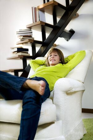 Portrait of young woman relaxing in chair at home  photo