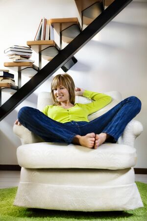 Portrait of young woman relaxing in chair at home Stock Photo - 3850656