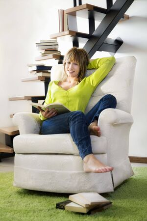 recline: Portrait of young woman relaxing and reading book in chair at home  Stock Photo