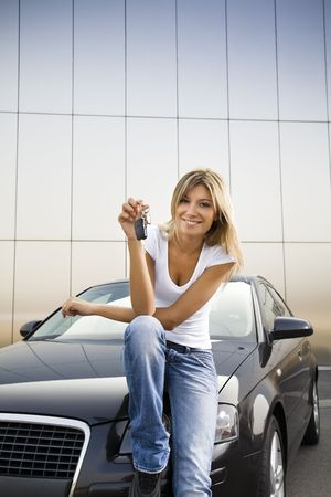 car keys: Young woman holding keys to new car