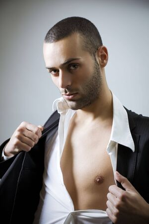 Portrait of young sexy man showing his bare chest and getting naked  photo