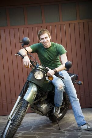 Portrait of young man sitting on vintage motorbike Stock Photo - 3881416
