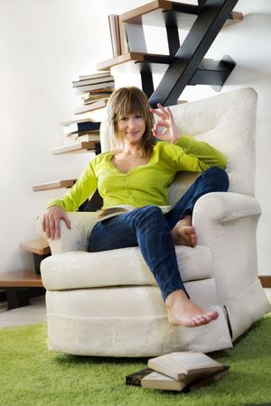 Portrait of young woman relaxing in chair at home Stock Photo - 3887317