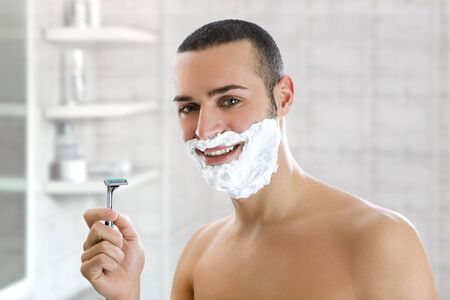 Young man shaving indoors. Copy space photo