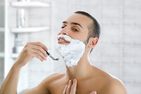 hombre afeitandose: Joven de afeitar adentro y sonriente. Copiar el espacio