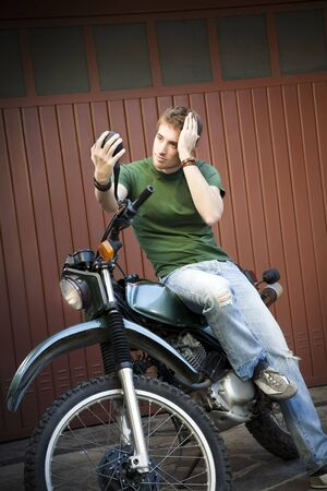 Portrait of young man sitting on motorbike and looking at mirror Stock Photo - 3896026