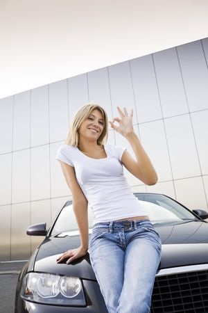 car keys: Young woman leaning on new car and similing Stock Photo