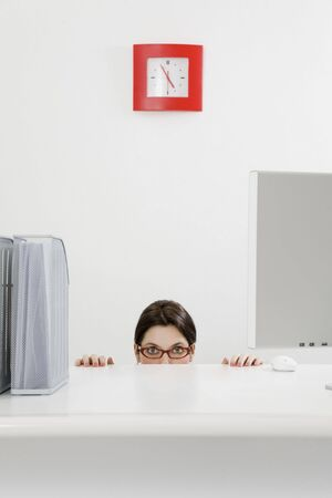 Young businesswoman hiding behind desk. Copy space photo