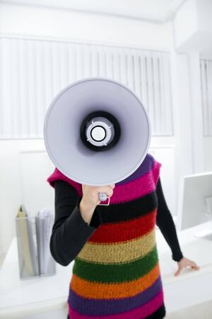 young businesswoman in office talking on the megaphone photo