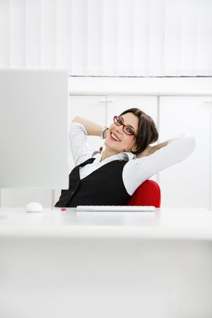 Young businesswoman relaxing in office, leaning on chair photo