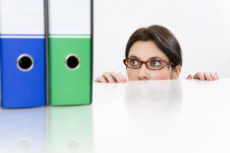 peering: Young businesswoman peering in curiosity from behind desk with folders