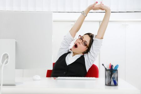 yawning: Young businesswoman sitting at desk yawning. Copy space