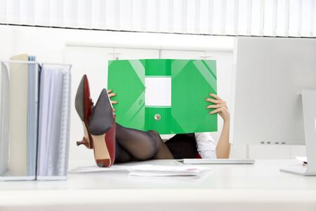 Young businesswoman sitting at desk with legs up and looking at folder photo