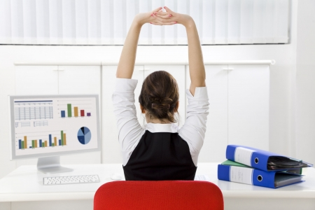 arms chair: Rear view of young businesswoman sitting at desk stretching. Copy space Stock Photo