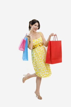 Mid adult Italian woman holding red shopping bags on white background Stock Photo - 3958972