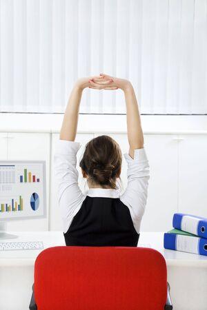 estiramientos: Parte trasera de la joven empresaria sesi�n de estiramiento en el escritorio. Copiar el espacio Foto de archivo