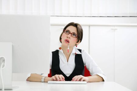 Young businesswoman in office typing on computer photo