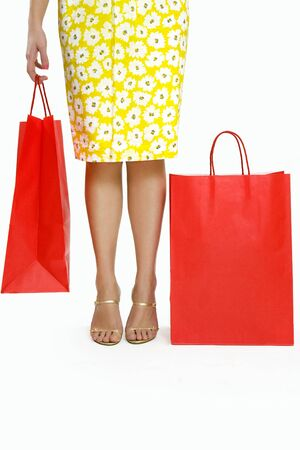cropped shots: Mid adult Italian woman holding red shopping bag on white background
