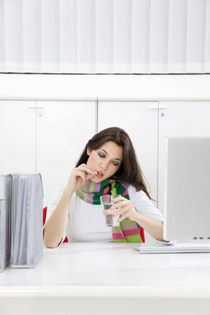 Close-up of young businesswoman putting pill in mouth in office Stock Photo - 3978654