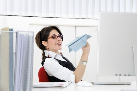 Young businesswoman throwing paper airplane in office photo