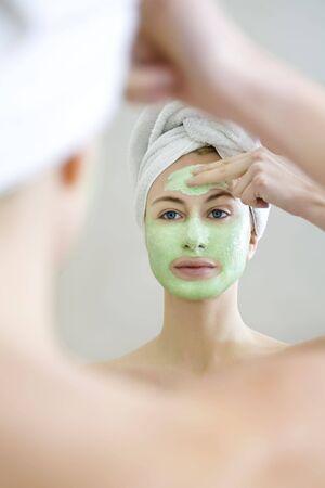 algas verdes: Joven mujer la aplicaci�n de algas verdes m�scara facial.