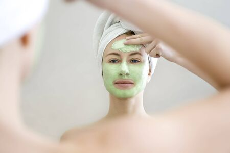 Young woman applying green algae facial mask.  photo