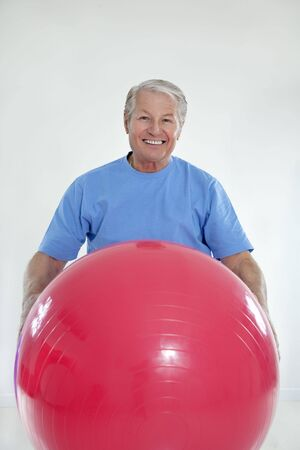 senior adult exercising with fitness ball in gym  photo