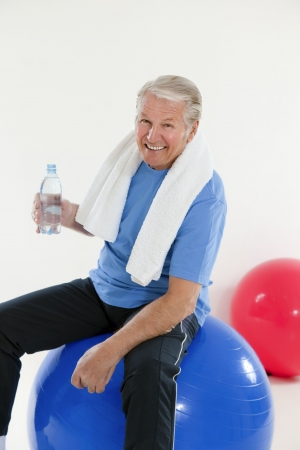 one senior adult man: senior adult sitting on fitness ball in gym and holding water bottle Stock Photo
