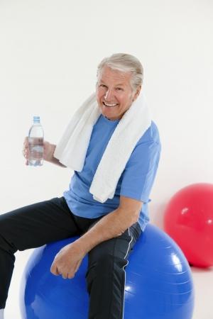 Senior Erwachsene Sitzung vom Fitness-Ball in der Turnhalle und Betrieb Wasserflasche