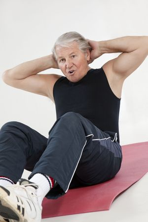 health club: senior man doing abs exercise in health club Stock Photo