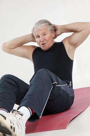 senior man doing abs exercise in health club Stock Photo