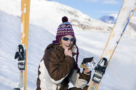 young woman eating chocolate bar on snow photo