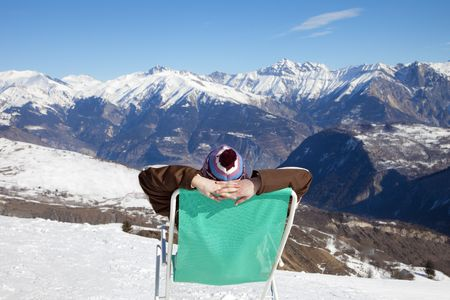 rear view of woman resting on chair in mountain