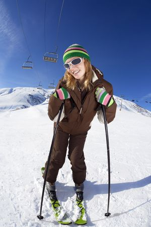 female skier leaning on sticks and smiling photo