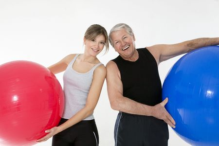 senior adult and daughter exercising with fitness ball in gym photo
