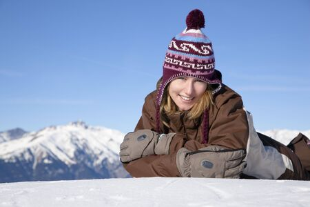 Young woman lying down on snow. Copy space photo