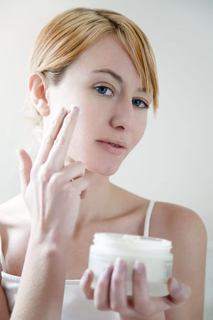 Young woman applying cream on her face. photo