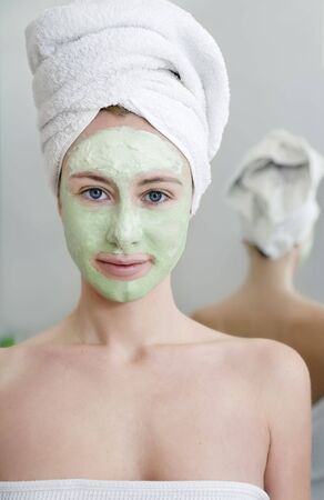 green algae: Young woman with facial mask in beauty spa.
