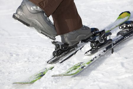 low section view: Low section view of woman unfastening her ski boots.