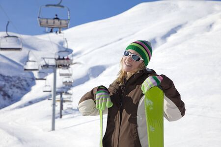 female skier leaning on skis and smiling photo