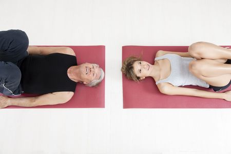 laying abs exercise: young woman and senior adult exercising in gym