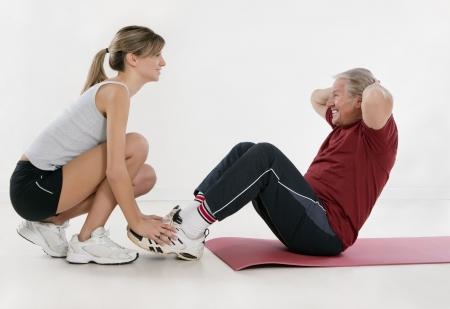 knees bent: personal trainer giovani adulti e anziani che esercitano in palestra Archivio Fotografico