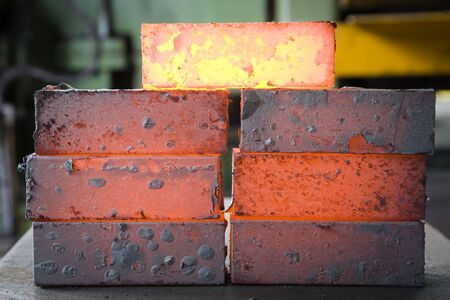 foundry: piles of hot iron blocks in foundry. Narrow focus on central block Stock Photo