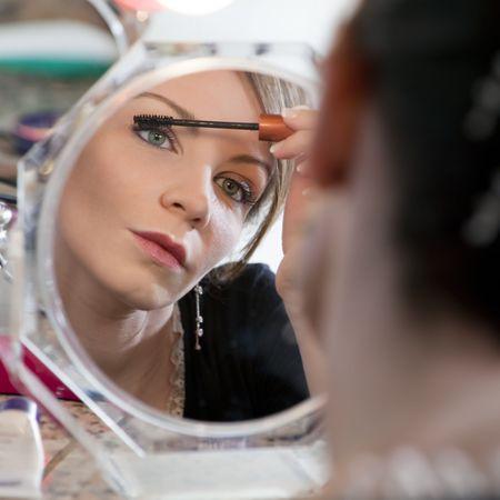 woman looking at mirror and applying make-up