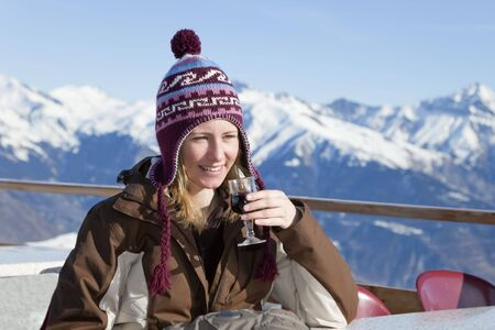 young woman enjoying red wine outdoors in mountain photo