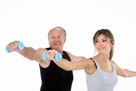 male senior adult: senior man and young woman exercising in gym. White background Stock Photo